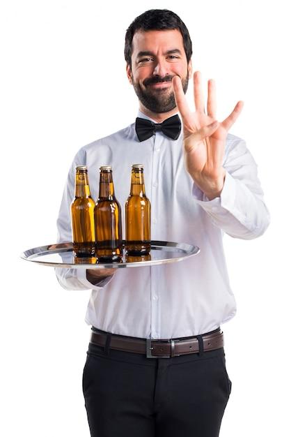 Serveur Avec Des Bouteilles De Bière Sur Le Plateau Comptant Quatre Photo gratuit
