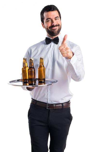 Serveur Avec Des Bouteilles De Bière Sur Le Plateau Avec Le Pouce Vers Le Haut Photo gratuit