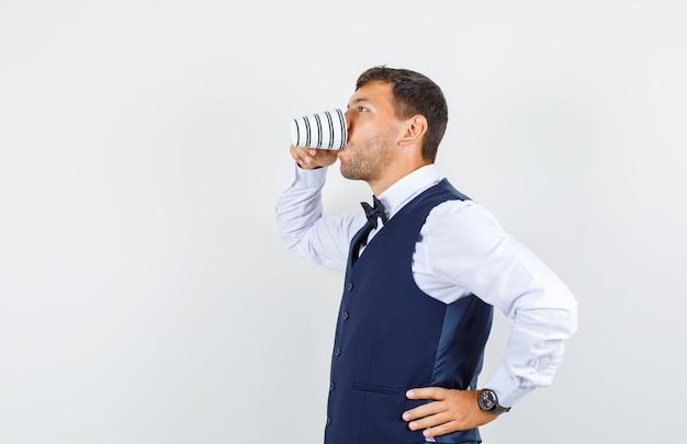 Serveur Buvant Une Tasse De Thé En Chemise Blanche, Gilet Bleu Foncé. Photo gratuit