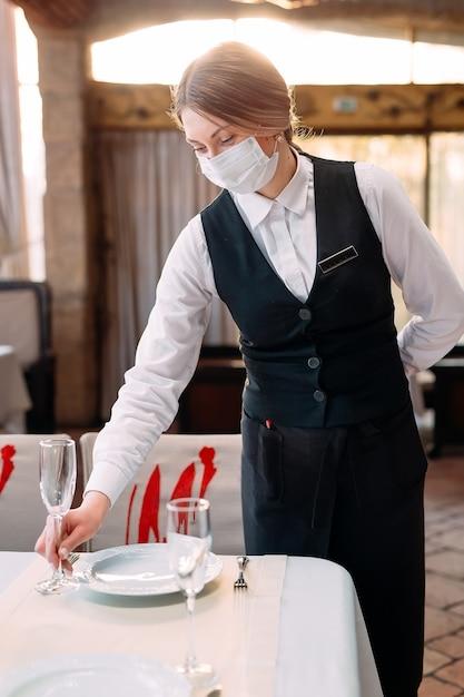 Un Serveur Dans Un Masque De Protection Médicale Sert La Table Dans Le Restaurant. Photo Premium