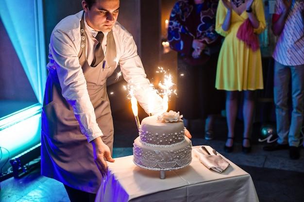 Le serveur fait un gâteau de mariage avec des bougies romaines Photo Premium