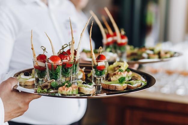 Un serveur garde un plateau avec des snacks Photo gratuit