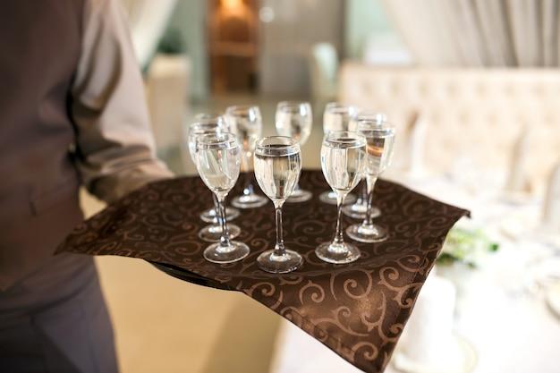 Serveur avec plateau accueille les visiteurs, verres remplis de vodka Photo Premium