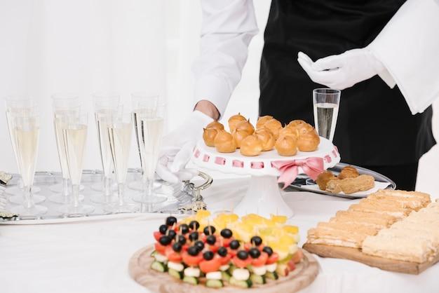 Serveur présentant un mélange de nourriture et de boissons sur une table Photo gratuit