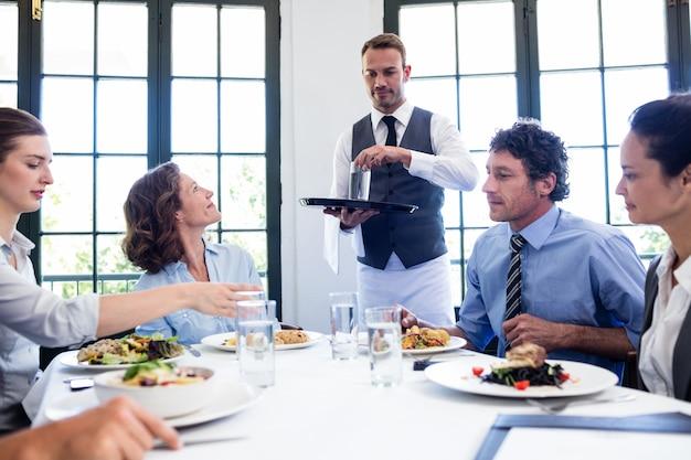 Serveur servant de l'eau à des hommes d'affaires Photo Premium