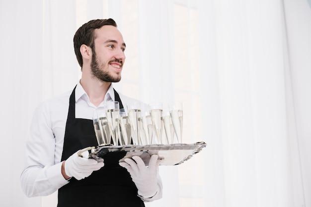 Serveur tenant un plateau avec des verres de champagne Photo gratuit