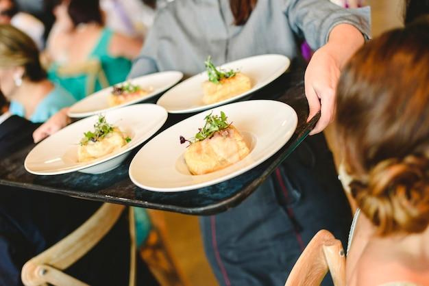 Des serveurs servant des assiettes d'apéritifs aux convives et invités à une fête. Photo Premium