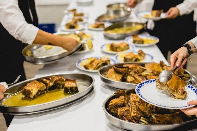 Serveurs servant des plats de viande lors d'un événement Photo Premium