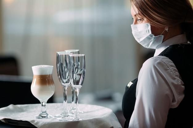 Serveuse D'apparence Européenne Dans Un Masque Médical Sert Du Café Au Lait. Photo Premium