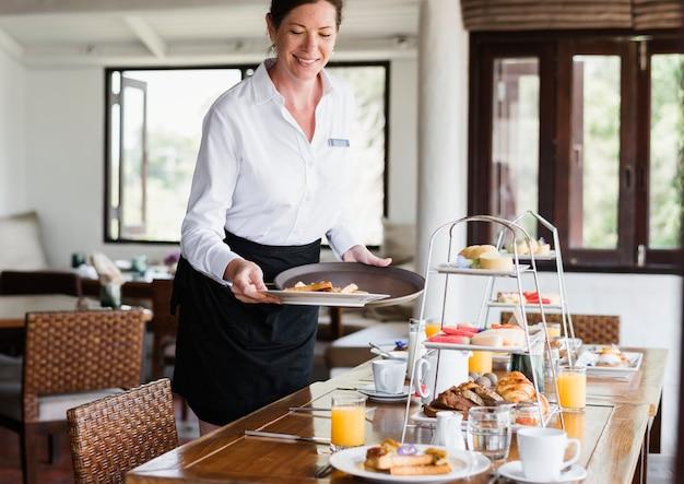 Serveuse d'hôtel servant de la nourriture Photo Premium