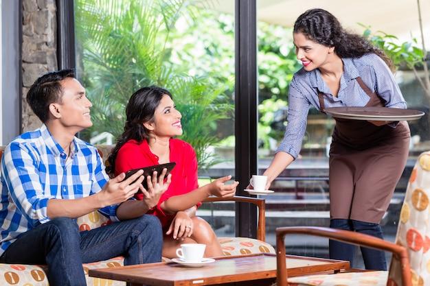 Serveuse indienne prenant des commandes au café ou au restaurant Photo Premium