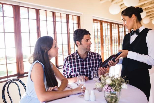 Serveuse montrant le vin au client à la table Photo Premium