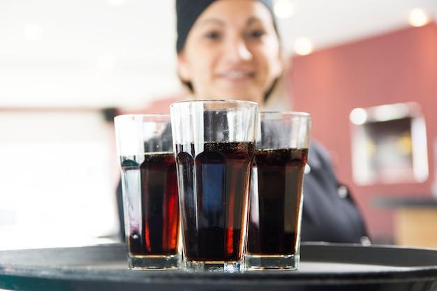 Serveuse offrant des verres de boisson sur le plateau Photo gratuit