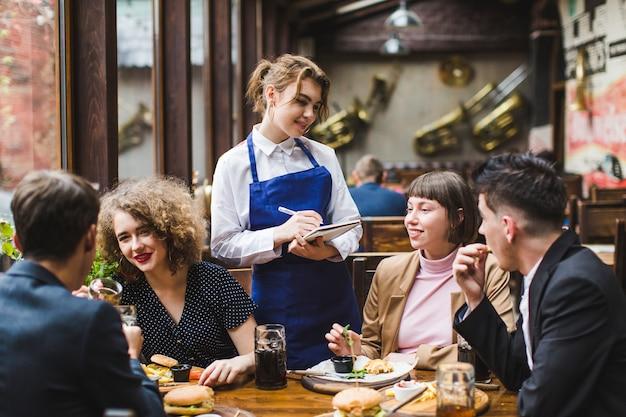 Serveuse Prenant Les Commandes Des Gens Au Restaurant Photo Premium