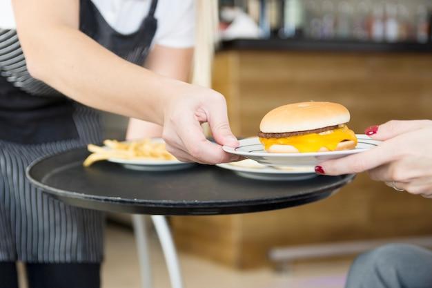 Serveuse servant un hamburger à une cliente du restaurant Photo gratuit