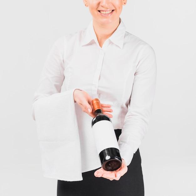 Serveuse tenant une bouteille de vin et souriant Photo gratuit