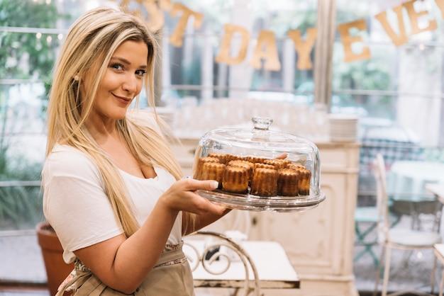 Serveuse tenant un plateau à muffins Photo gratuit