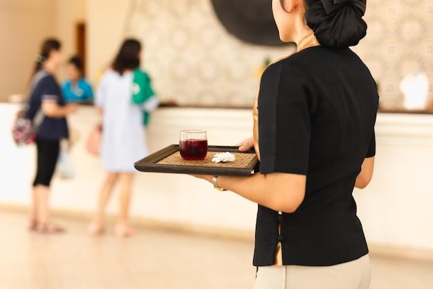 Serveuse avec un verre de bienvenue sur un plateau à hotle Photo Premium