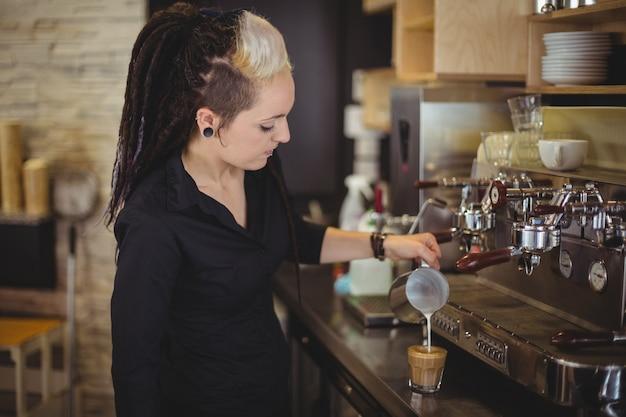 Serveuse verser le lait dans une tasse de café au comptoir Photo gratuit