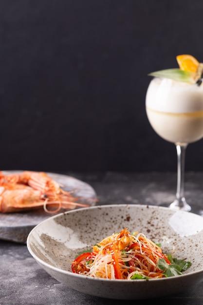 Servi à Table Au Restaurant. Salade Funchoza Aux Crevettes Et Légumes Aux Graines De Sésame, Grosses Crevettes Corail Et Verre à Cocktail. Photo Premium