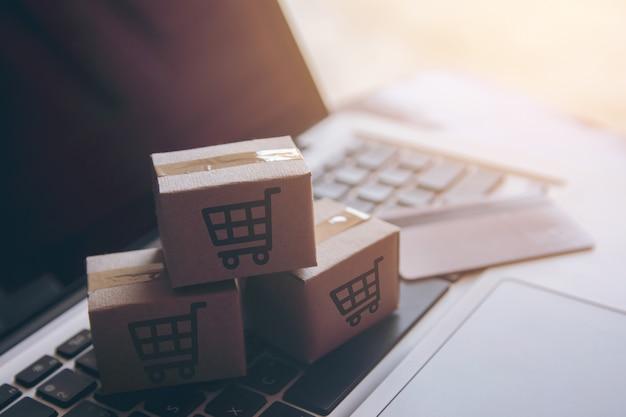 Service d'achat sur le web en ligne. avec paiement par carte de crédit et offre la livraison à domicile. colis ou cartons de papier Photo Premium