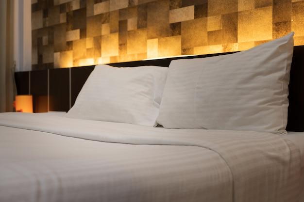 Le service d'étage des chambres installe un oreiller blanc sur le lit de l'hôtel Photo Premium