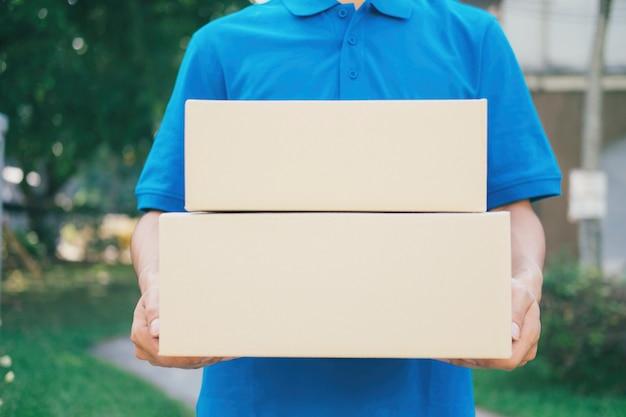 Service de livraison de courrier debout devant la maison avec des boîtes. Photo Premium