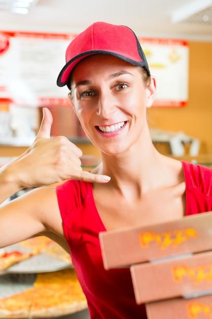 Service de livraison, femme tenant des boîtes à pizza Photo Premium