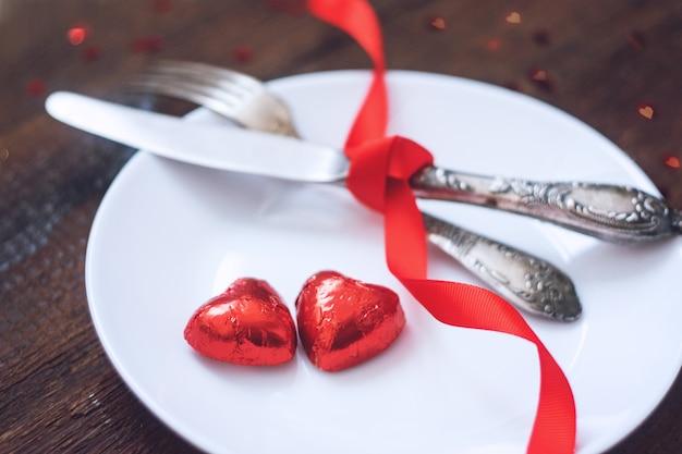Service De Table De Fête Pour La Saint-valentin, Maquette Avec Deux Bonbons Au Chocolat En Forme De Cœur Rouge Photo Premium