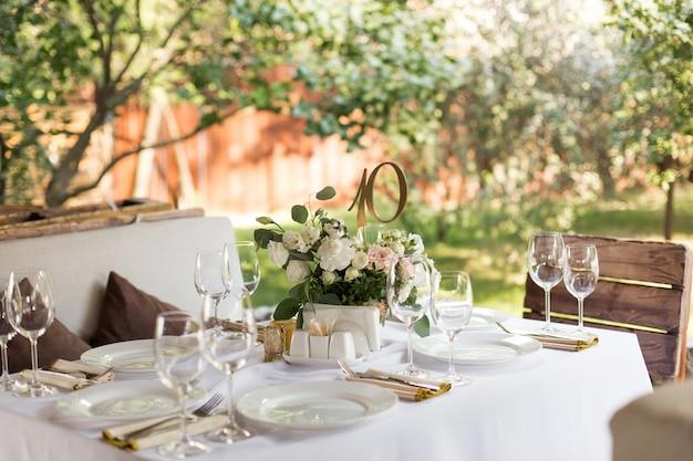 Service de table de mariage décoré de fleurs fraîches dans un vase en laiton. fleuristerie de mariage. table de banquet pour les invités à l'extérieur avec vue sur la nature verdoyante. bouquet de roses, eustoma et feuilles d'eucalyptus Photo Premium
