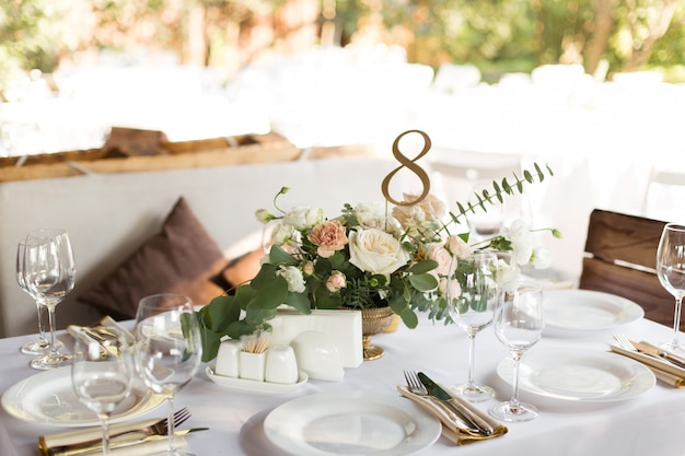 Service de table de mariage décoré de fleurs fraîches dans un vase en laiton. table de banquet pour les invités à l'extérieur Photo Premium