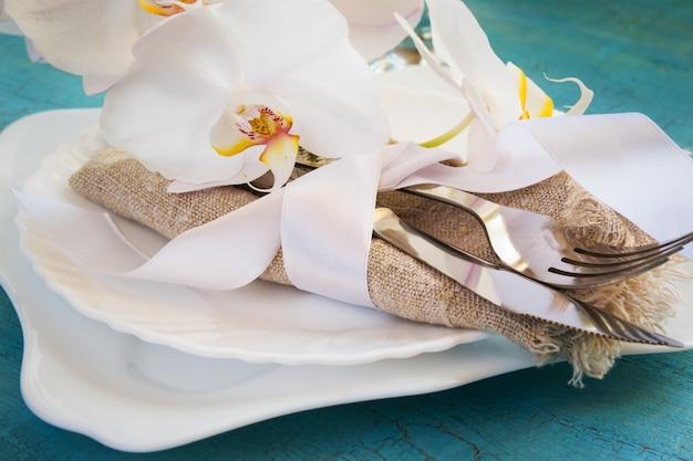 Service de table à ressort avec décorations et serviettes de table en orchidée blanche Photo Premium