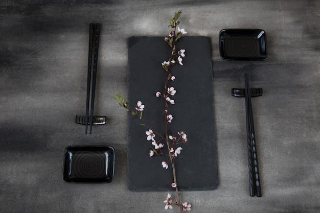 Service de table de style japonais: bâtons de sushi, assiettes et une branche de cerisier en fleurs Photo Premium