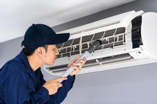 Service technique utilisant un aspirateur pour nettoyer le climatiseur Photo Premium