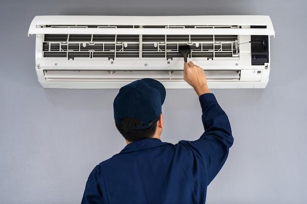 Service technique utilisant une brosse pour nettoyer le climatiseur Photo Premium