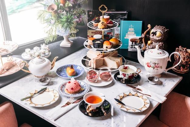 Service à thé anglais comprenant thé chaud, pâtisseries, scones, sandwichs et mini-tartes. Photo Premium