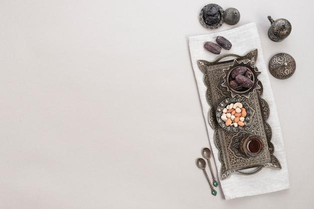 Service à thé arabe traditionnel; des noisettes; dates et thé sur un plateau métallique sur fond blanc Photo gratuit