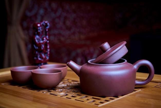 Service à thé en argile se dresse sur une planche de bois. Photo Premium