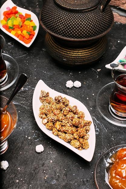 Service à thé avec beaucoup de confiture de gelée de couleur sucrée, bonbons susam, citron, confiture de pêche Photo gratuit