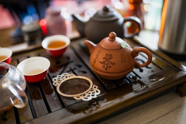 Service à thé chinois avec une passoire métallique sur un plateau en bois Photo gratuit