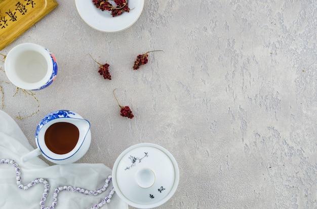 Service à thé en porcelaine de chine bleu et blanc avec des herbes sur fond de béton gris Photo gratuit