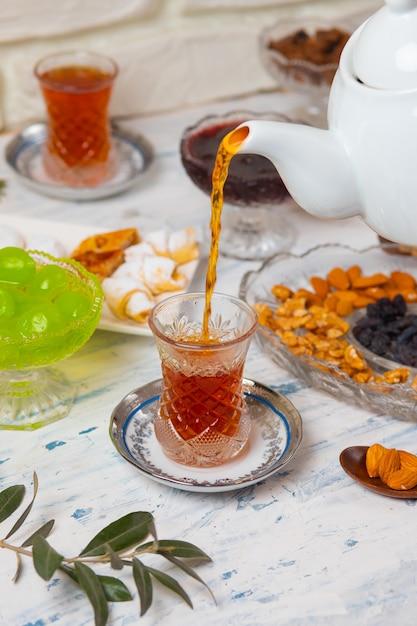 Service à thé avec des variétés de noix traditionnelles, citron, confiture et bonbons servis sur une nappe blanche Photo gratuit