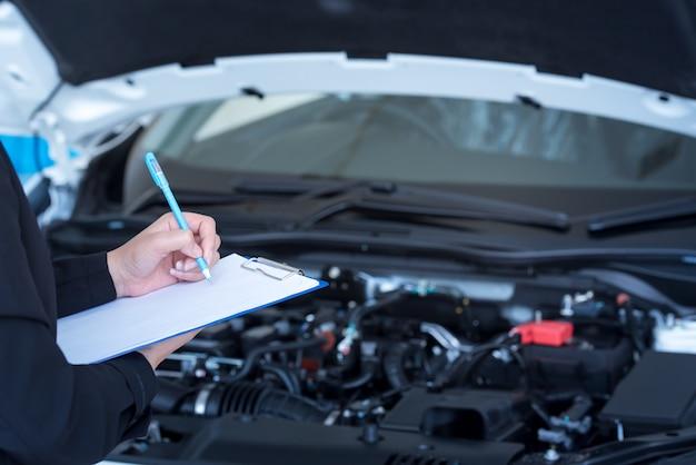 Service de voiture, réparation, concept de maintenance - mécanicien automobile asiatique ou smith écrivant dans le presse-papiers d'un atelier ou d'un entrepôt, technicien effectuant la liste de contrôle pour la réparation d'une machine neuve Photo Premium
