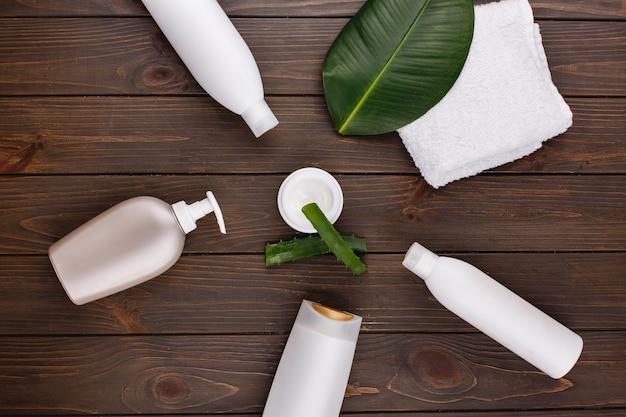 Serviette blanche, bouteilles de shampooing et revitalisant allongé sur une table avec feuille verte et aloès Photo gratuit