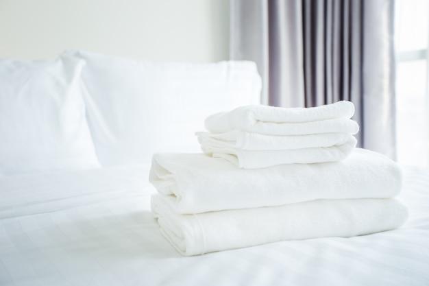 Serviette blanche sur un lit blanc dans la chambre Photo Premium