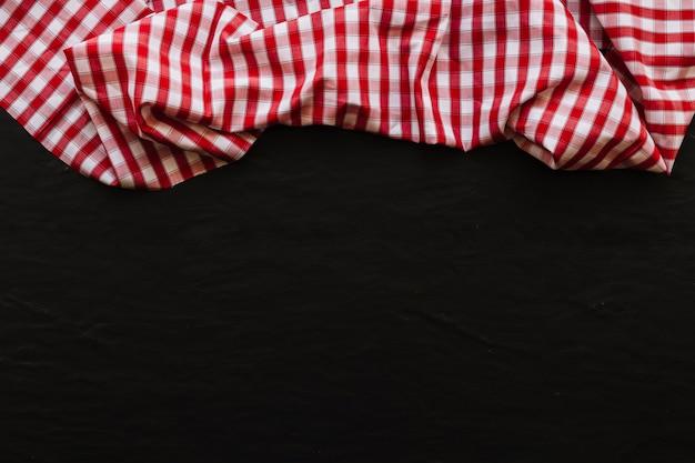 Serviette à carreaux drapée sur fond noir Photo gratuit