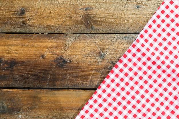 Serviette en damier rouge plié sur une table en bois Photo gratuit