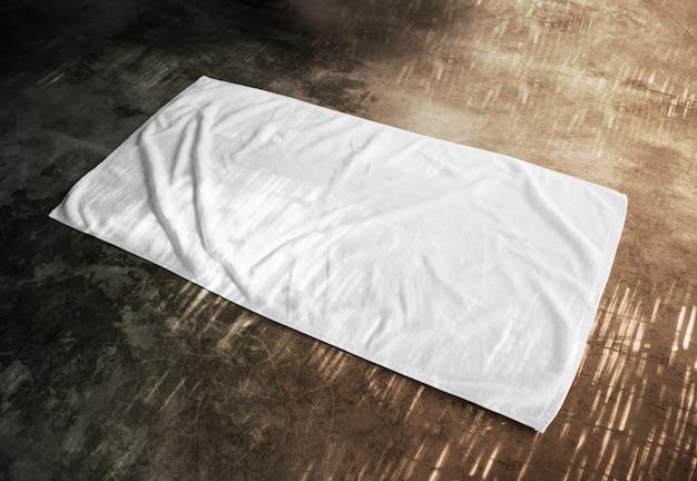Serviette de plage blanche vierge sur sol texturé Photo Premium