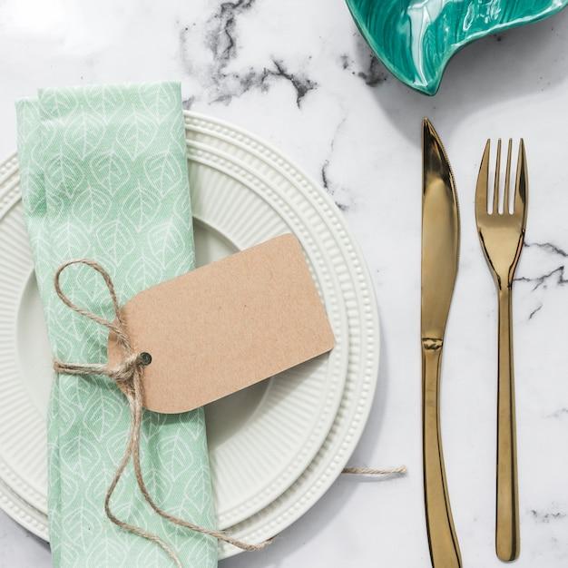 Serviette pliée attachée avec une étiquette vierge sur une assiette et des couverts sur un fond texturé en marbre Photo gratuit