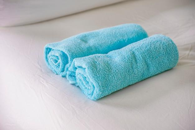 Serviettes bleues sur lit blanc Photo Premium